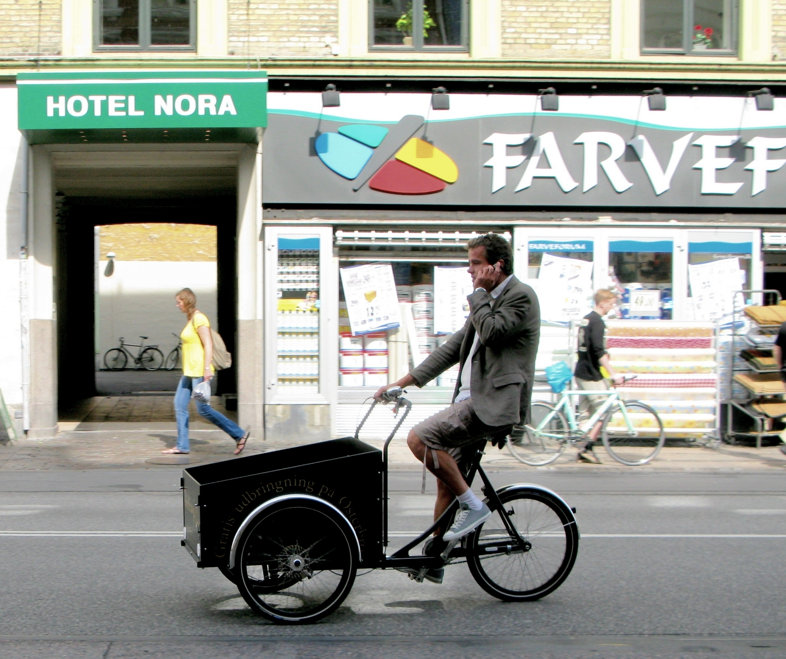 A man riding a cargo bike and making a phone call