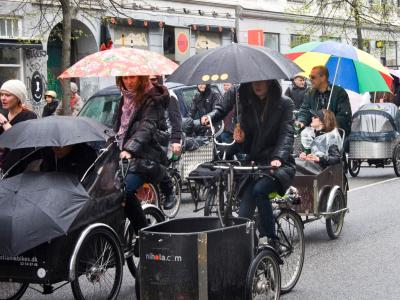 muliple cargo bikes in the rain, the people are using one hand to hold an umbrella and the other one is on the handbar